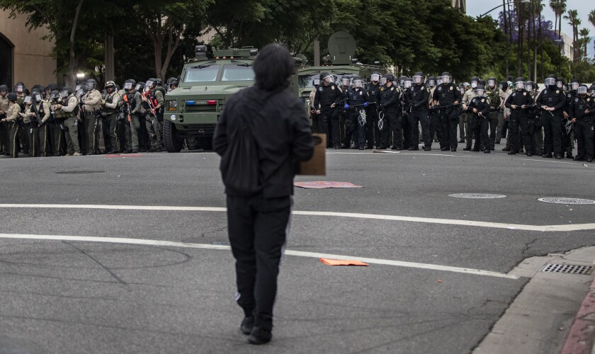 A protester faces a line of law enforcement personnel in Riverside on Monday.