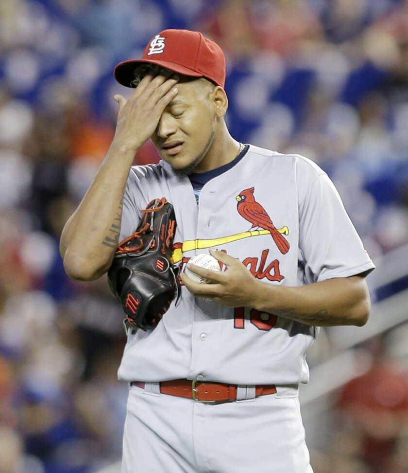 St. Louis Cardinals' Carlos Martinez wipes his face after allowing a double by Miami Marlins' Marcell Ozuna in the first inning of a baseball game, Sunday, July 31, 2016, in Miami. (AP Photo/Alan Diaz)