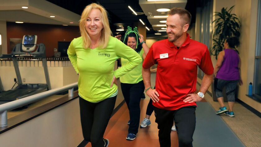 "Beth Thorp, left, with trainer Paul Carey exercises with other members of the ""Lucky 13"" team at Tri-City Wellness Center in Carlsbad on Monday night. Each year, Tri-City Medical Center chooses 13 former patients to train for the Carlsbad Half-Marathon."