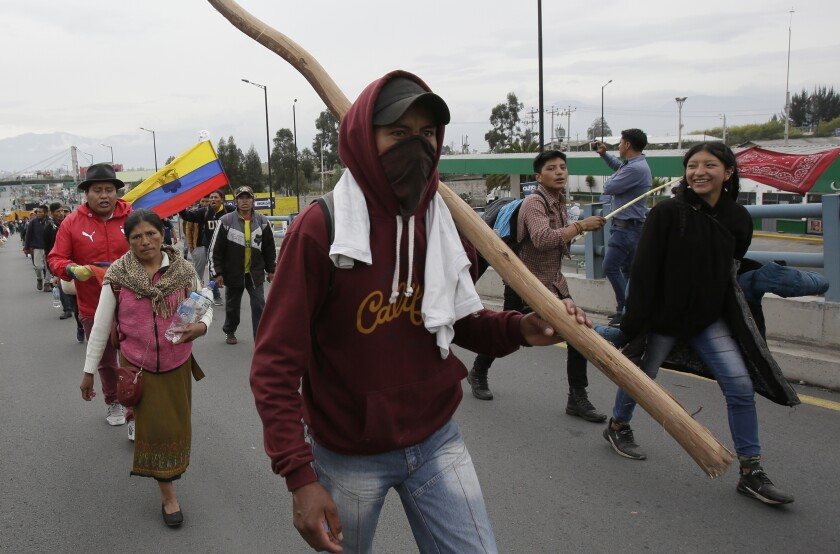 Indigenous anti-government protesters arrive by foot in Quito, Ecuador, Tuesday, Oct. 8, 2019. Ecuador has endured days of popular upheaval since President Lenin Moreno scrapped fuel price subsidies, a step that set off protests and clashes across the small South American country. (AP Photo/Dolores Ochoa)