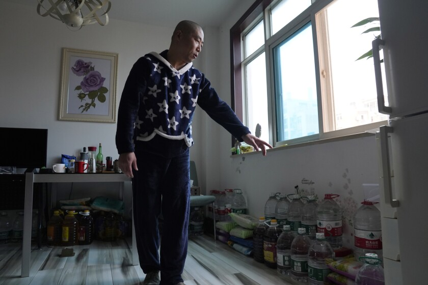 Zhu Tao of Wuhan, China, points to his stockpile of supplies in his home.