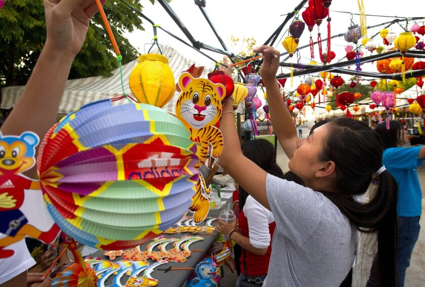 Anh Duong, a student at Hoover High School, hangs lanterns.