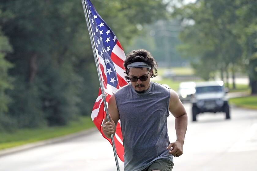 A man jogs along a Houston road with an American flag on Saturday.