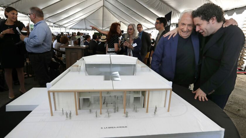 At right, Gustavo Dudamel embraces architect Frank Gehry as they view Gehry's model for the new YOLA Center.
