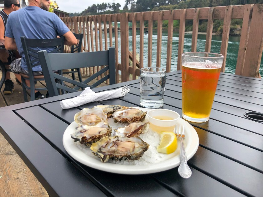 A plate of oysters and a glass of beer on the dining deck at the Noyo River Grill.