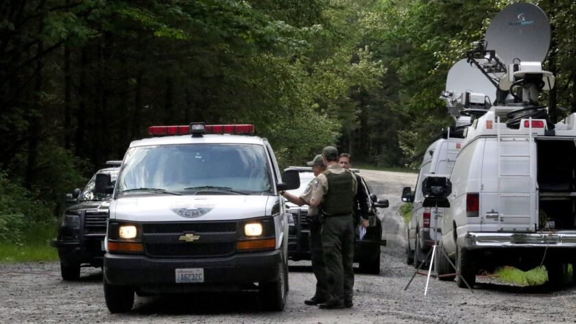 Washington State Fish and Wildlife Police confer with an individual from the King County Medical Exa