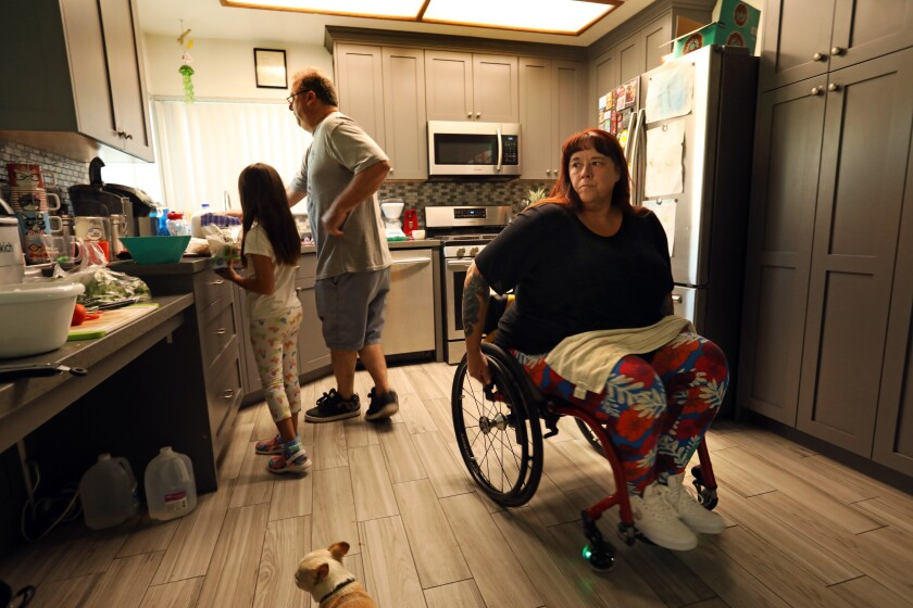 """LANCASTER, CALIFORNIA-MAY 17, 2021-Lenora Lewis prepares dinner for her family as her husband Sean Lewis helps their granddaughter, Lilliana Vega, age 6, who lives with them. Lenora Lewis, who lives in Lancaster, went to Dr. Mukesh Misra for a spinal fusion to treat her degenerative disc disease and lower back pain. When she woke up from the surgery on Sept. 10, 2013, she was paralyzed from the waist down. """"Every day, I have to wake up and deal with the ramifications of what he did to me,"""" she said. """"Every single day, I have to deal with this. There is no amount of money that anyone could ever pay me for what he did to me. I will always be like this. And it's because of him."""" (Carolyn Cole / Los Angeles Times)"""