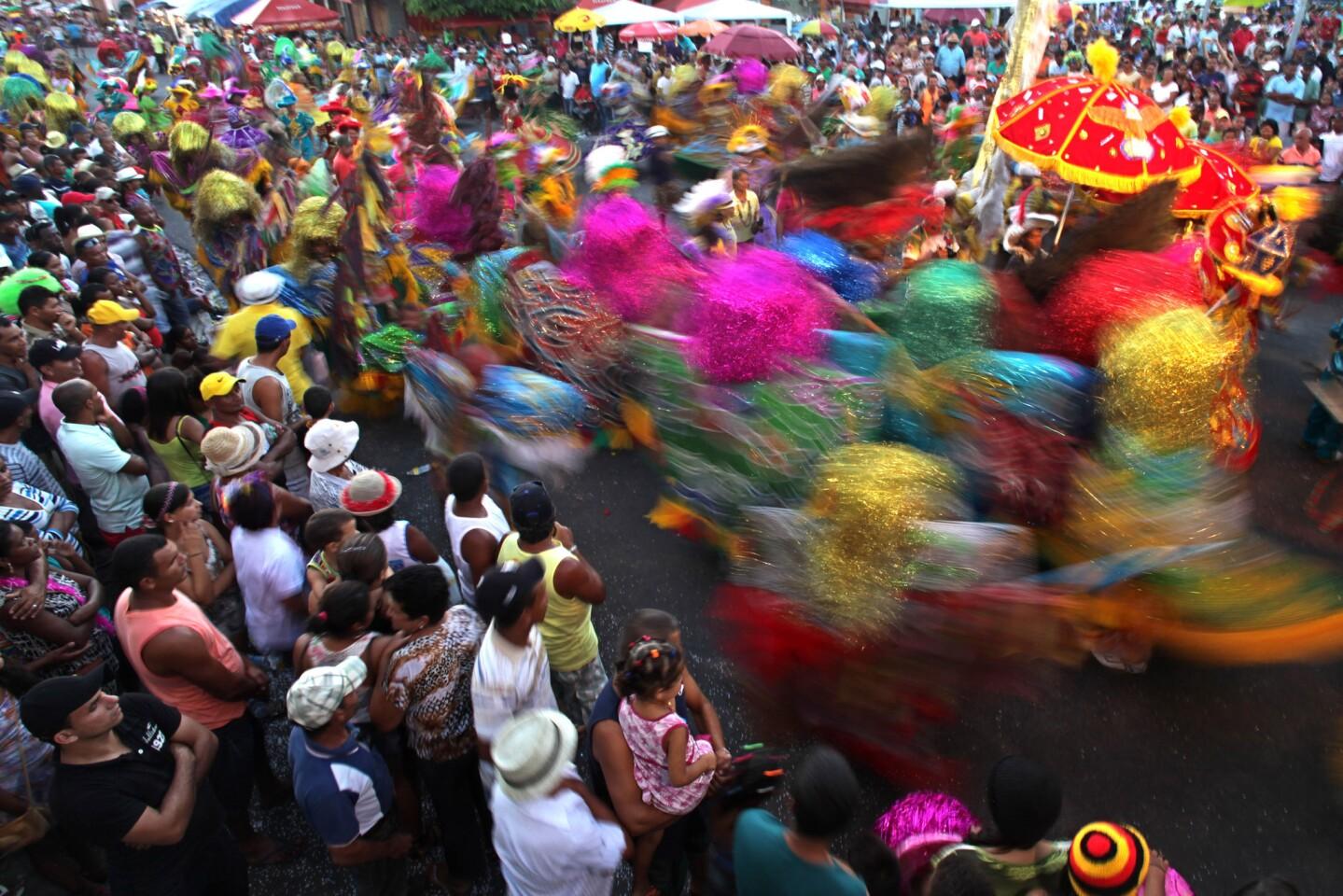 En esta imagen, tomada el 8 de febrero de 2016, el público observa la actuación de un grupo de bailarines maracatus durante el carnaval de Nazare da Mata, en Brasil. La ciudad del estado de Pernambuco, en el noreste de Brasil, es considerada la cuna del maracatu, una danza de ritmo frenético y origen africano que caracteriza al peculiar carnaval de la zona. (Foto AP/Eraldo Peres)