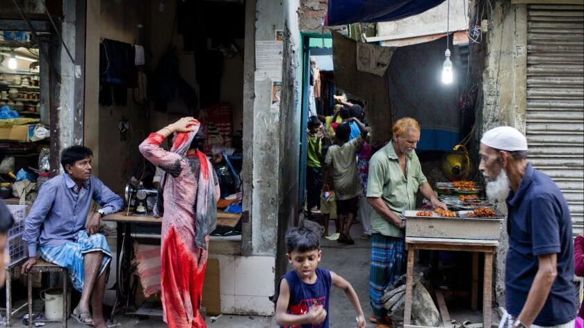 Residents walk past a man making barbecue in an alley at the Mohammadpur Geneva camp, where over 100