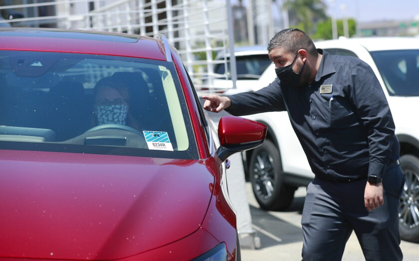 Kari Dart gets ready do take a test drive as Javier Hernandez helps her at John Hine Mazda in Mission Valley. Dart took the test drive alone to maintain social distancing under a borrowed car agreement.