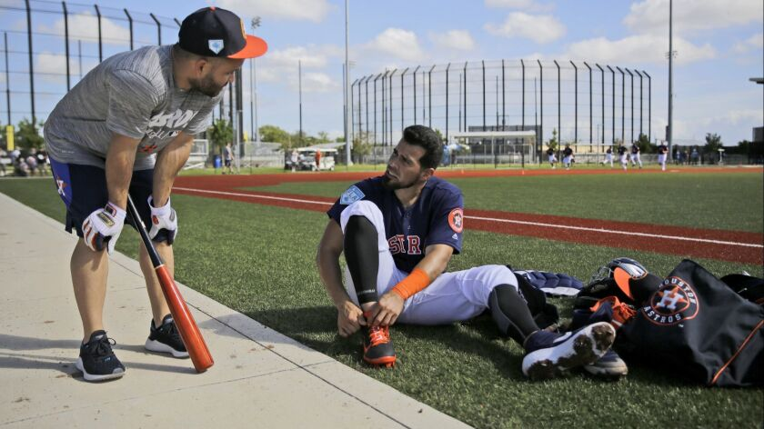 Houston Astros infielder Jose Altuve, left, talks with teammate Robinson Chirinos as Chirinos ties h