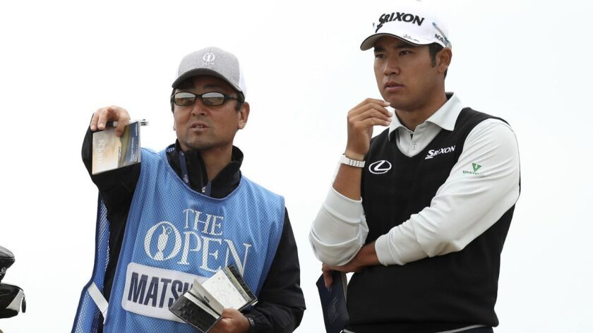 Hideki Matsuyama of Japan and his caddie look along the 3rd fairway during a practice round ahead of