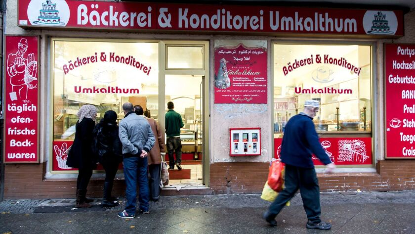 People look through the window of a Lebanese confectionery at Sonnenallee in the Neukoelln district of Berlin.