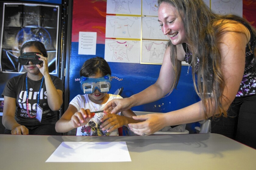 Laura Smith-Velazquez, a candidate for the Mars One mission, works with Haley Rodriguez, 8, and Gabriela Jimenez, 16, as they attempt to draw a smiley face while wearing prism glasses at Girls Inc. on Friday.