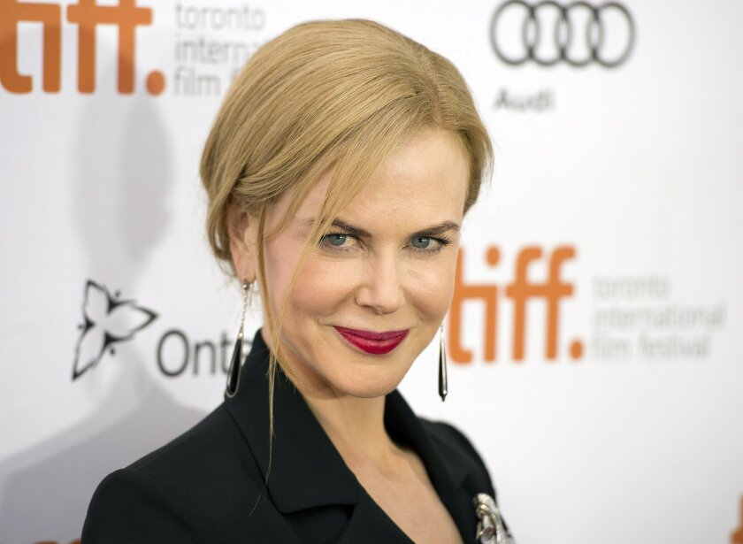 """FILE - In this Sept. 6, 2013 file photo, Nicole Kidman poses for a photograph on the red carpet at the gala for the new movie """"The Railway Man"""" during the 2013 Toronto International Film Festival in Toronto. For her latest role in """"The Railway Man,"""" out Friday, April 11, 2014, the 46-year-old Academy Award winner plays supportive wife to World War II veteran Eric Lomax (portrayed by Colin Firth). In the autobiographical adaptation, Patti and Eric Lomax confront his past as a prisoner of war in Thailand, where he worked on the """"death railway,"""" a 258-mile stretch of treacherous train track running into Burma. (AP Photo/The Canadian Press, Frank Gunn, file)"""