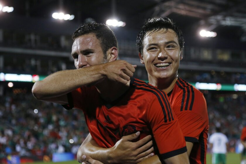 Mexico defenseman Miguel Layun, left, celebrates with forward Erick Torres after Layun's goal against Bolivia in the first half of an international friendly soccer game in Commerce City, Colo., on Tuesday, Sept. 9, 2014. (AP Photo/David Zalubowski)
