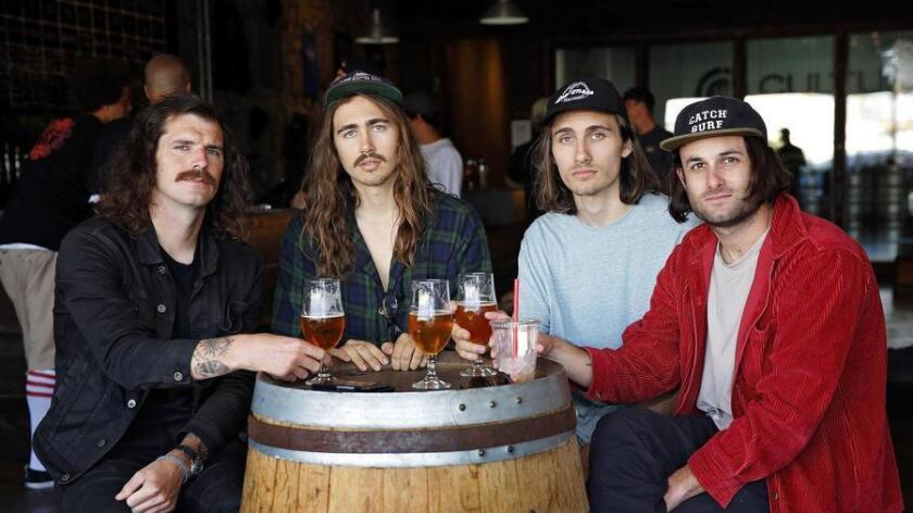 Members of The Gloomies grab drinks at Culture Brewing in Ocean Beach. Chris Trombley (from left) enjoys a Mosaic IPA, Blake Martz a blonde, his brother, Grant Martz has a pale ale and Andy Craig finishes off his previously purchased iced coffee. (Nancee E. Lewis)