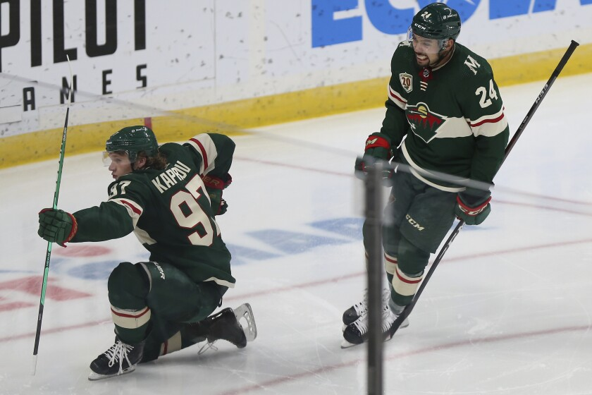 Minnesota Wild's Kirill Kaprizov (97) celebrates on the ice with Matt Dumba (24) after scoring a goal during the third period of the team's NHL hockey game against the Vegas Golden Knights on Wednesday, March 10, 2021, in St. Paul, Minn. Minnesota won 4-3. (AP Photo/Stacy Bengs)