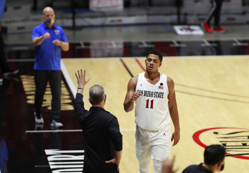 SDSU senior Matt Mitchell walks off the court as coach Brian Dutcher waves to UCLA coach Mick Cronin.