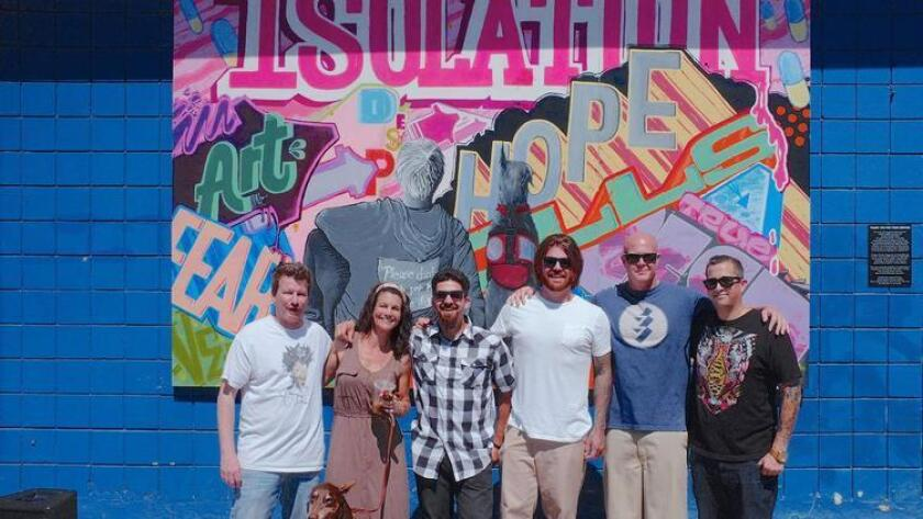 John Murphy (from left) Elizabeth Washburn, Daniel Lopez, Christopher Tomlin, Justin Greenlund and Aaron Raher in front of a Combat Arts mural on the side of the Adams Ave. Car Wash in Normal Heights. The mural was unveiled during Art Around Adams on June 4, 2016. (David Melchior)