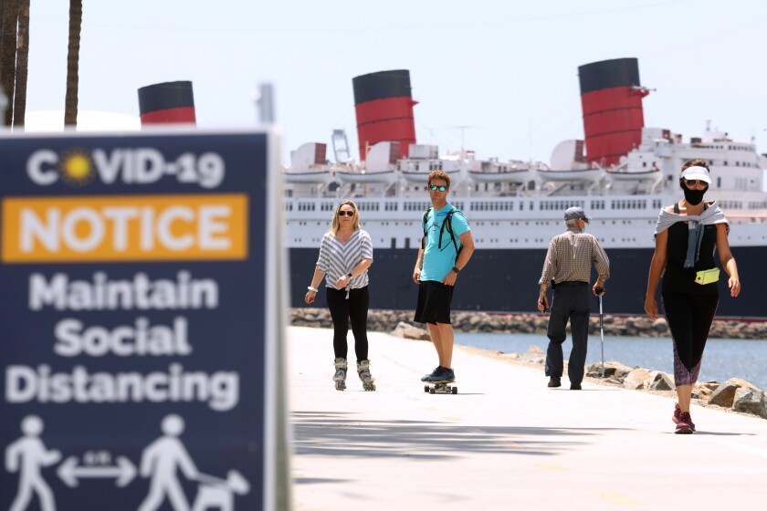 LONG BEACH, CA - MAY 11, 2020 - - Scially distanced bikers and walkers, against a backdrop of the Queen Mary, make their way along pedestrian and beach bike path on the first day that Long Beach reopened the path on Monday May 11, 2020. The city of Long Beach eased a few of its public health restrictions, allowing under certain guidelines the reopening of pedestrian and beach bike paths, tennis centers and courts. Beach bathrooms are also reopening, but the parking lots and beaches still remain closed. (Genaro Molina / Los Angeles Times)