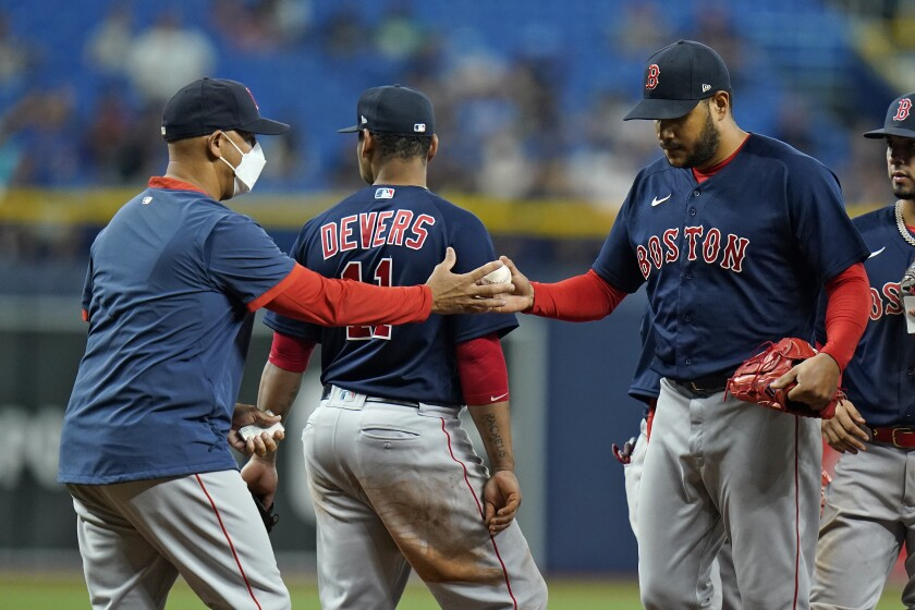 Boston Red Sox manager Alex Cora, left, takes the ball from starting pitcher Eduardo Rodriguez as he is taken out of the game against the Tampa Bay Rays during the seventh inning of a baseball game Thursday, Sept. 2, 2021, in St. Petersburg, Fla. (AP Photo/Chris O'Meara)