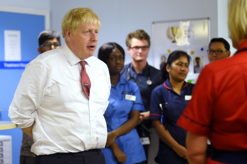 "Britain's Prime Minister Boris Johnson speaks to mental health professionals during his visit to Watford General Hospital, in Watford, Monday, Oct. 7, 2019. Britain and the European Union appeared to be poles apart Monday on a potential Brexit deal, with the Dutch government urging the British government to offer ""more realism and clarity,"" and U.K. Prime Minister Boris Johnson insisting the bloc has to soften its stance. (Peter Summers/Pool Photo via AP)"
