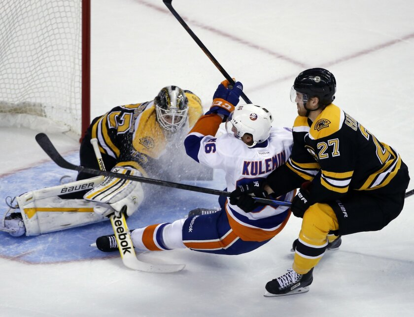 New York Islanders left wing Nikolai Kulemin (86) is checked to the ice by Boston Bruins defenseman Dougie Hamilton (27) during a bid to score against Bruins goalie Niklas Svedberg in the first period of an NHL preseason hockey game in Boston, Tuesday, Sept. 30, 2014. (AP Photo/Elise Amendola)