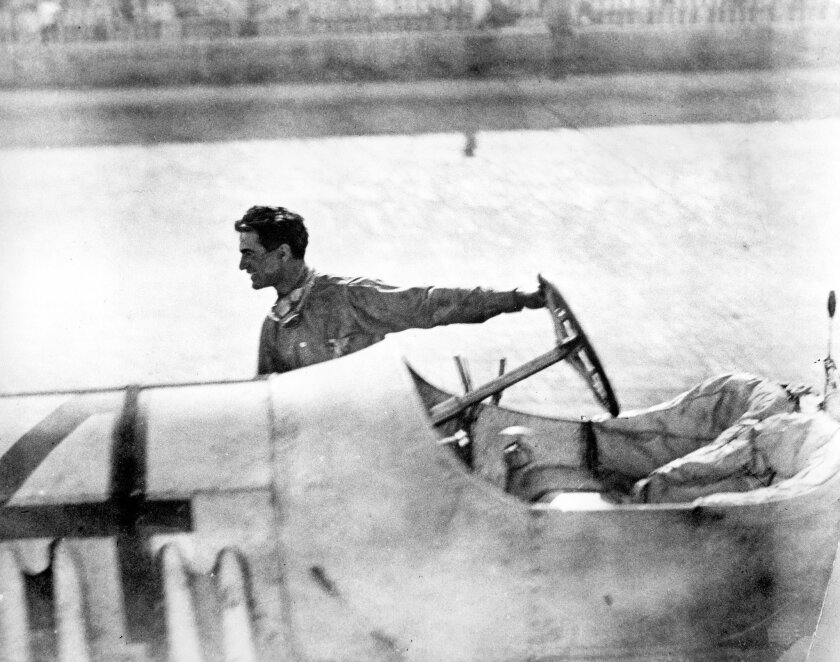 FILE - In this May 30, 1912, file photo, Ralph DePalma pulls his race car across the finish line after it broke down with two laps remaining in the Indianapolis 500 auto race in Indianapolis, Ind. Joe Dawson won the race.  (AP Photo/File)