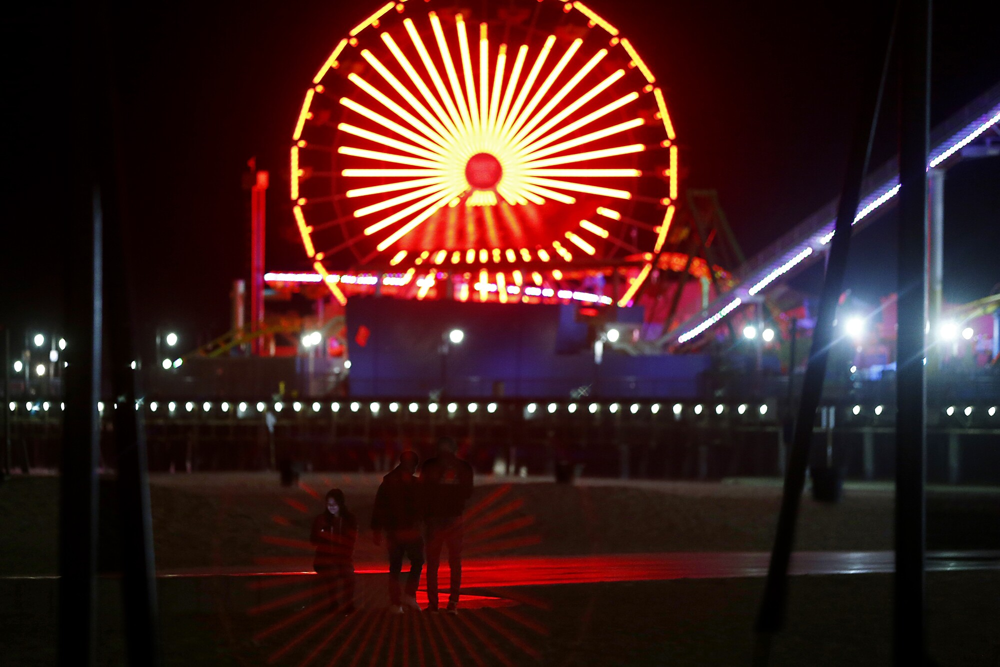 Youths violate a beach closure in Santa Monica as the coronavirus stay-at-home order continues in Southern California.