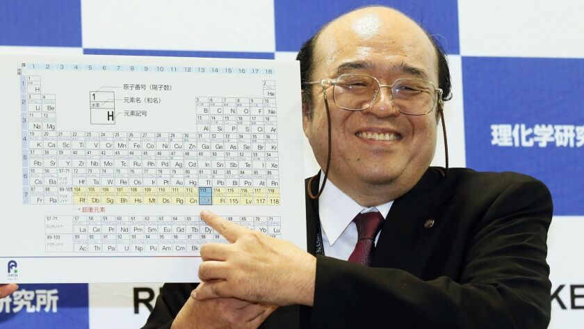 Kosuke Morita of Riken Nishina Center for Accelerator-Based Science points at periodic table of the