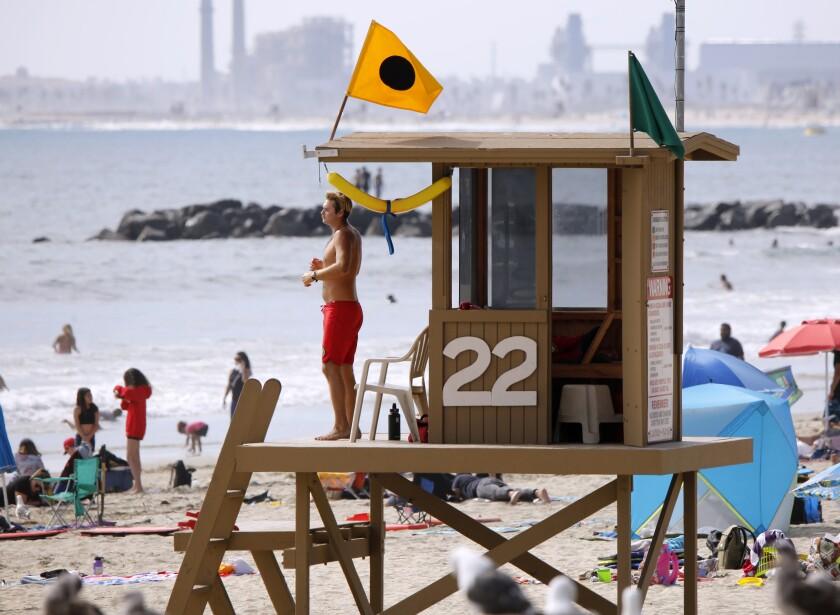 A Newport Beach lifeguard keeps an eye on beachgoers Wednesday.