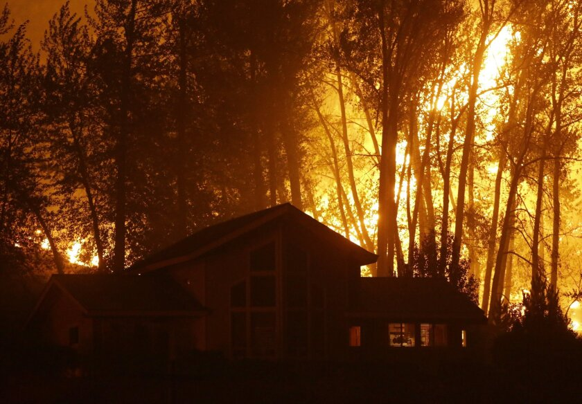 A wildfire burns behind a home in Twisp, Wash.