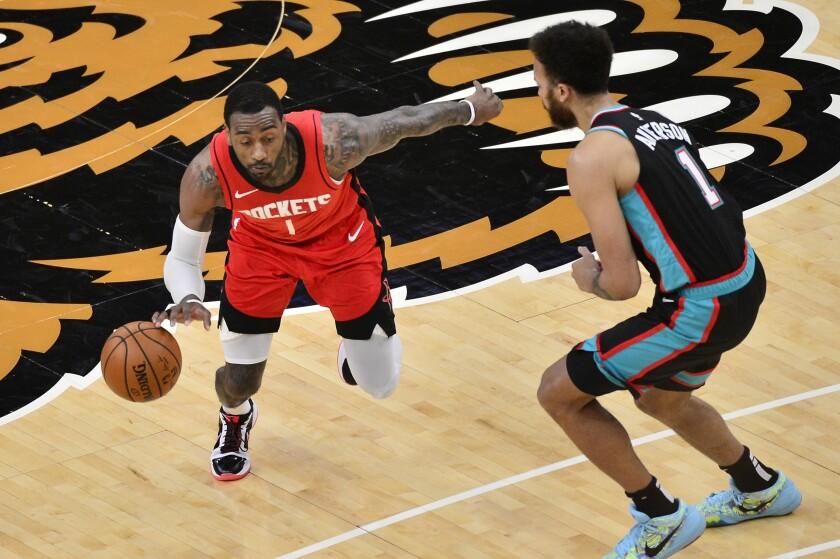 Houston Rockets guard John Wall, left, handles the ball against Memphis Grizzlies forward Kyle Anderson in the second half of an NBA basketball game Thursday, Feb. 4, 2021, in Memphis, Tenn. (AP Photo/Brandon Dill)