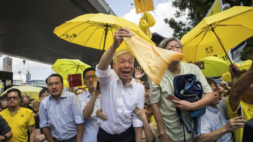 Occupy Central leader Chu Yiu-ming, center, reacts as he waves a yellow towel towards a prison van c
