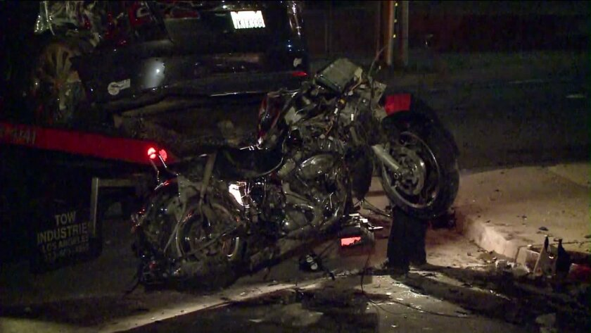 A motorcycle is loaded onto a tow truck following a fatal hit-and-run crash in Pasadena on Thursday.