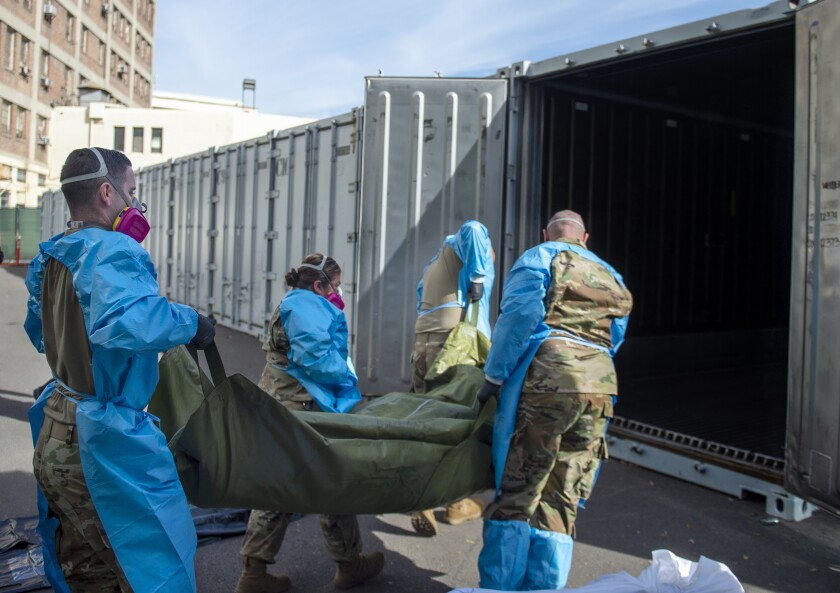 FILE - This Jan. 12, 2021, file photo provided by the LA County Dept. of Medical Examiner-Coroner shows National Guard members assisting with processing COVID-19 deaths and placing them into temporary storage at LA County Medical Examiner-Coroner Office in Los Angeles. Just a few months ago, California was the epicenter of the coronavirus pandemic in the U.S. Now as cases spike in other parts of the country, California has gone from worst to first with the lowest infection rate in the U.S. even as it moves toward a broader reopening of its economy. (LA County Dept. of Medical Examiner-Coroner via AP, File)