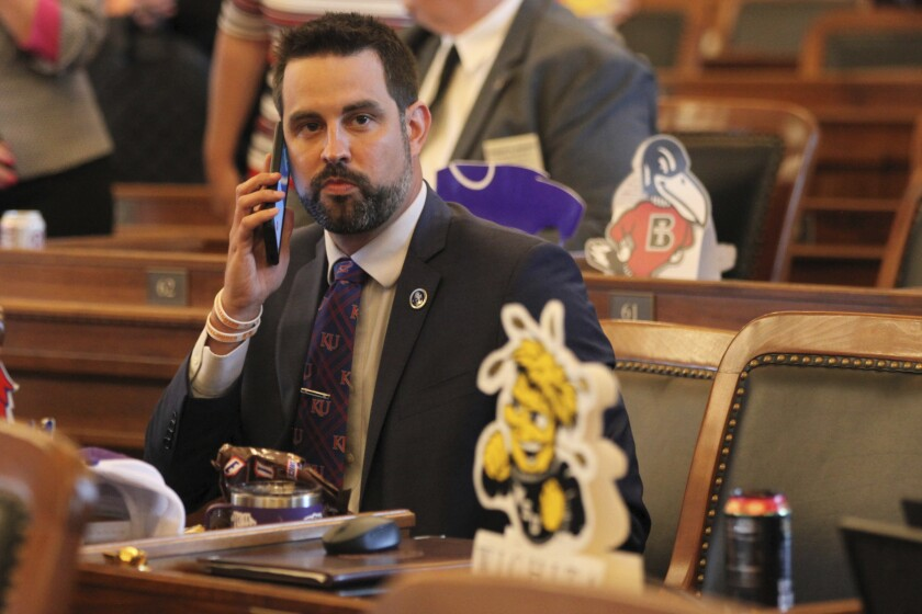 In this photo from Monday, May 3, 2021, Kansas state Rep. Mark Samsel, R-Wellsville, talks on his cellphone ahead of the House's daily session, at the Statehouse in Topeka, Kan. Samsel has been charged with three counts of misdemeanor battery over incidents involving two teenage students while he was substitute teaching. (AP Photo/John Hanna)