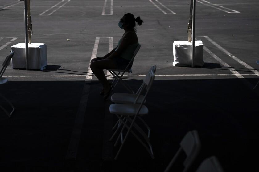 ARCHIVO - En esta imagen de archivo del 28 de agosto de 2021, una mujer en una zona de espera tras recibir una vacuna contra el COVID-19 en una clínica instalada en el estacionamiento de CalOptima en Orange, California. (AP Foto/Jae C. Hong, Archivo)