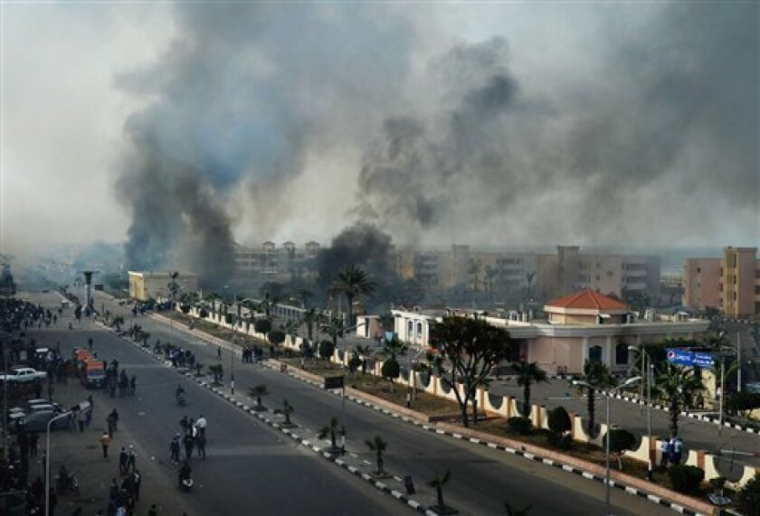 FILE - In this Sunday, Jan. 27, 2013 file photo, smoke rises after Egyptian protesters clash with police, unseen, in Port Said, Egypt. The military intervened in clashes between thousands of protesters and police in the restive Egyptian canal city of Port Said on Sunday, March 3, 2013, the latest in a cycle of violence that killed several security members and civilians, and which continues to rock Egypt two years after the uprising that ousted longtime ruler Hosni Mubarak. (AP Photo, File)