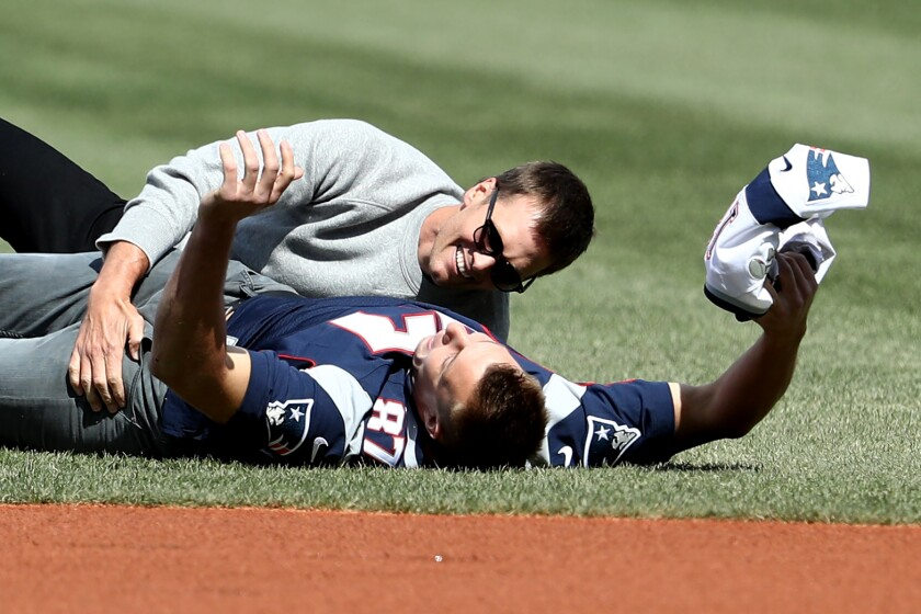 Rob Gronkowski of the New England Patriots is tackled by Tom Brady before the Opening Day game between the Boston Red Sox and the Pittsburgh Pirates at Fenway Park on April 3, 2017.