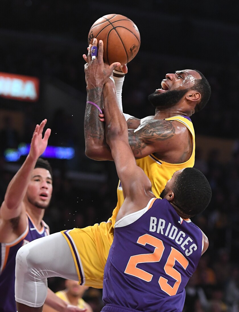Lakers' LeBron James is fouled by Phoenix Suns' Mikal Bridges while driving to the basket in the third quarter at Staples Center on Monday
