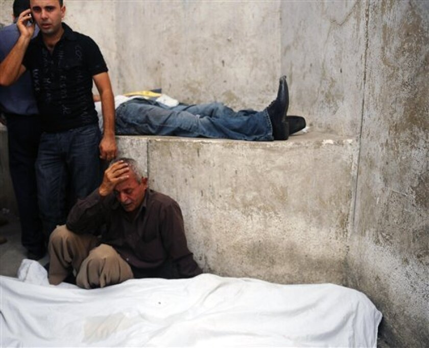 A man grieves near the shrouded bodies of protesters killed during clashes with Egyptian security forces in Cairo Egypt, Sunday, Oct. 9, 2011. Fierce clashes erupted Sunday between Christians protesting a recent attack on a church and the Egyptian military, leaving more than 19 people dead and scores injured, Health Ministry officials said. (AP Photo)