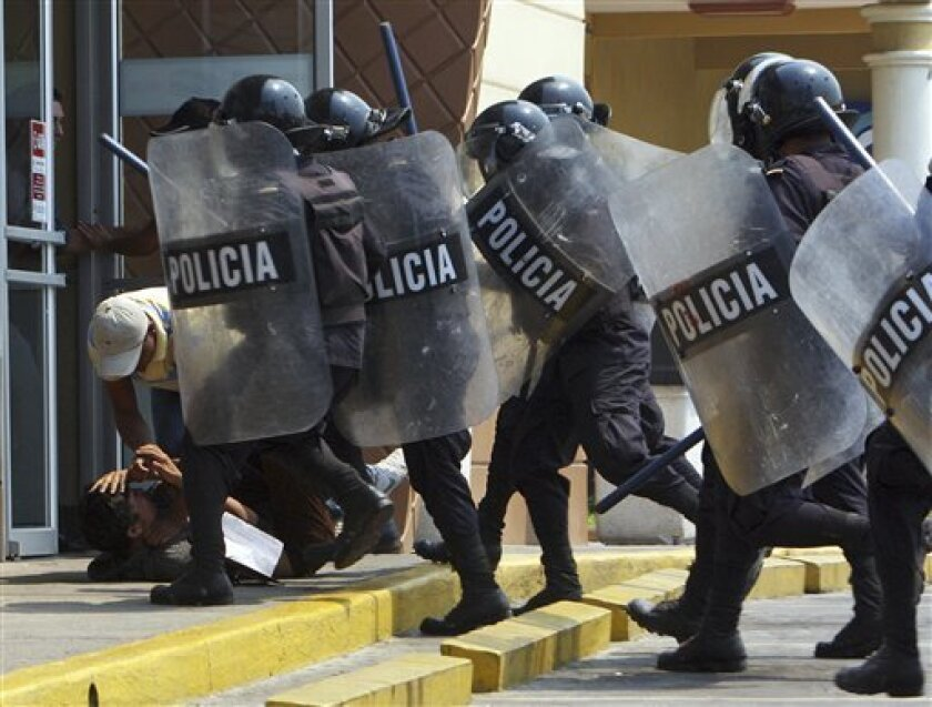 Plainclothes and riot police detain a protester during a general strike in Tegucigalpa, Honduras, Wednesday March 30, 2011. Union workers, farmers and other organizations demanding better education, an increase in the minimum wage and against fuel price hikes clashed with police as they tried to bl