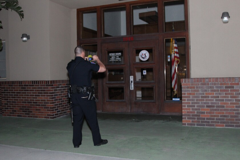 A police officer takes photos after responding to a reported vandalism at the Democratic Party of Orange County headquarters in the city of Orange.