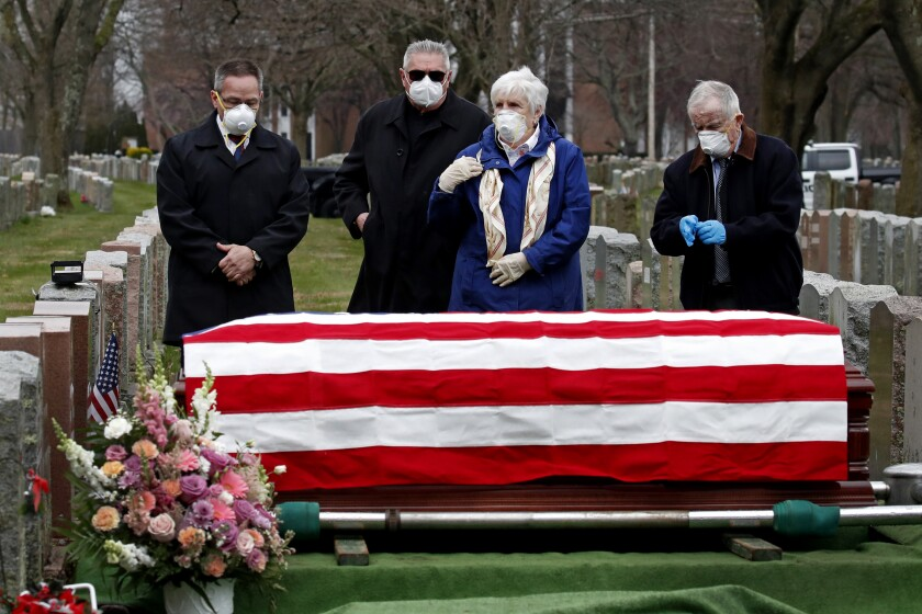 Four mourners stand next to a U.S.-flag-draped casket of a military veteran in a cemetery