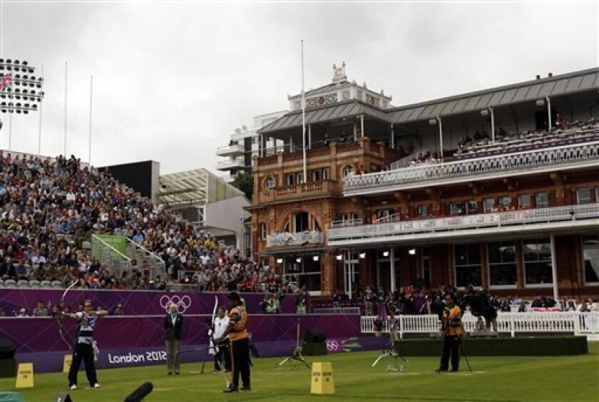 Lord's Cricket Ground hosts amatch between England's Laurence Godfrey, at left, and Malaysia's Khairul Anuar Mohamad, center, during the men's individual archery competition at the 2012 Summer Olympics, Friday, Aug. 3, 2012, in London. (AP Photo/Marcio Jose Sanchez)