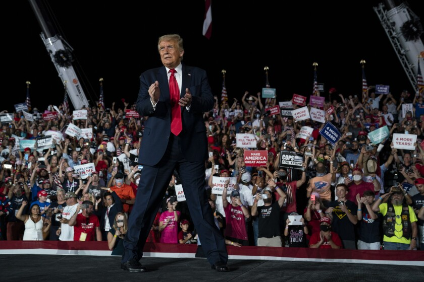 President Trump walks off clapping as a crowd cheers at a campaign rally at Orlando Sanford International Airport on Monday.