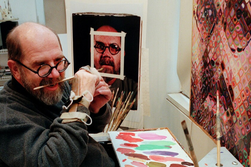 Chuck Close uses a hand brace to hold his paint brush