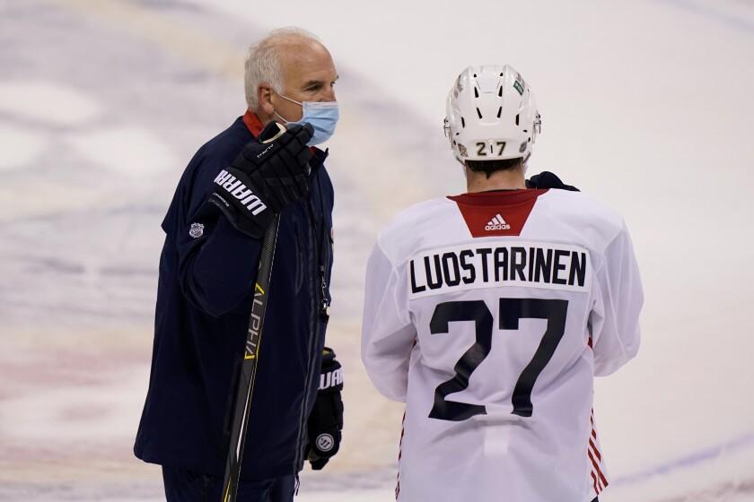 Florida Panthers head coach Joel Quenneville, left, talks with center Eetu Luostarinen (27) during NHL hockey training camp, Tuesday, Jan. 5, 2021, in Sunrise, Fla. (AP Photo/Lynne Sladky)